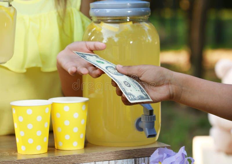 卖自然柠檬水的女孩对非裔美国人的男孩在公园 r 库存图片