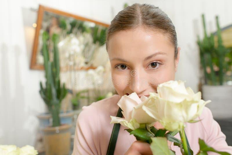 卖花人嗅到的白玫瑰 免版税库存照片