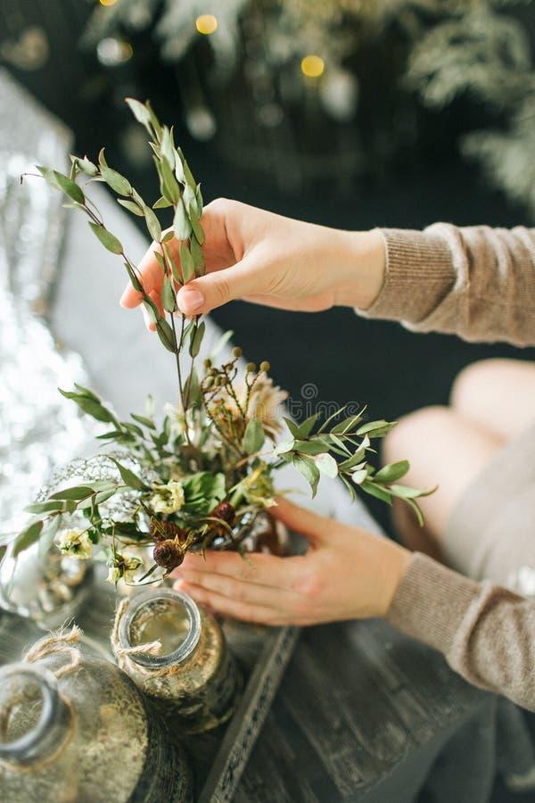 卖花人女性与在木桌上的花装饰一起使用 免版税库存图片
