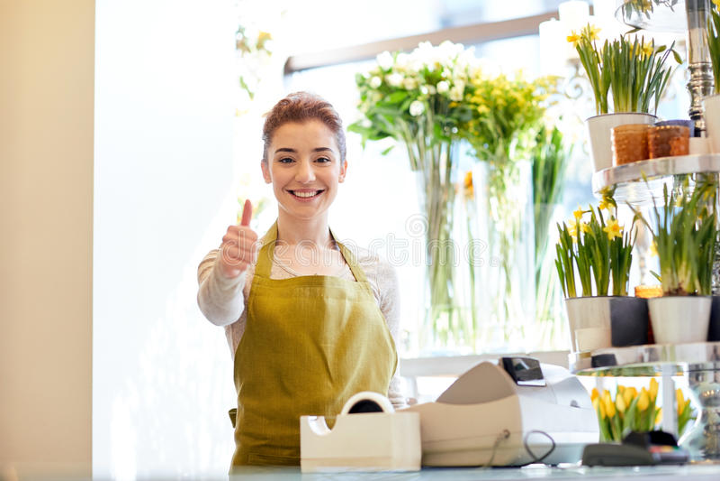 卖花人妇女在显示赞许的花店 免版税库存图片