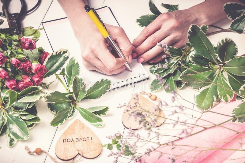 卖花人工作 写下命令玫瑰和绿叶的花束妇女的手 小企业概念 免版税图库摄影