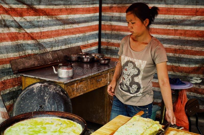 卖蛋薄煎饼的少女在地方街市上 免版税库存图片