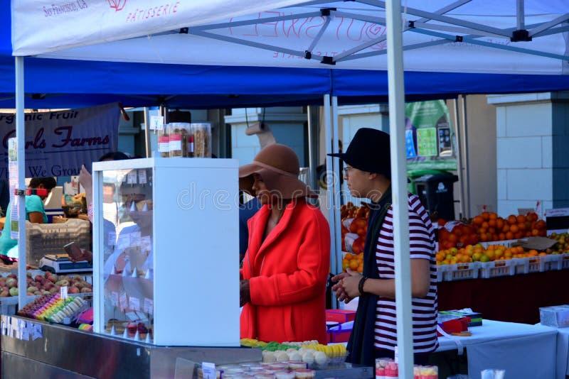 卖食物的俏丽的夫人在有机农夫市场上 免版税库存照片