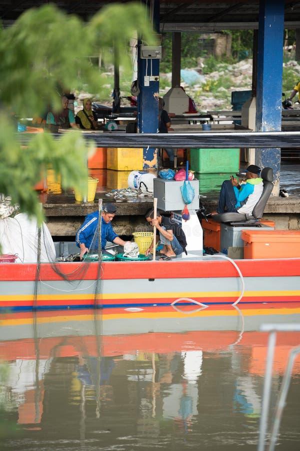 卖鱼的渔夫在码头 免版税库存照片