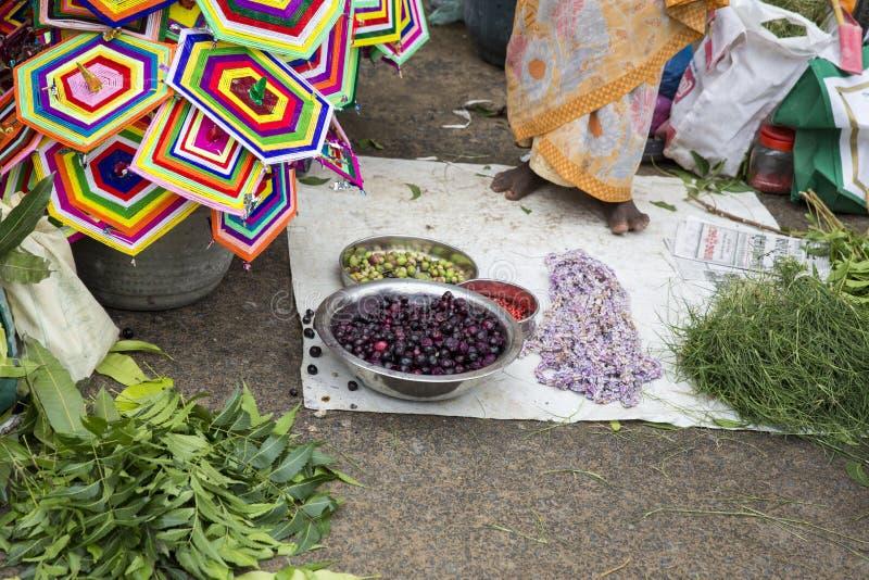 卖鲜花,菜,果子,献身者的伞的供营商能保佑印度神Ganesh在地方市场上在第一天 免版税库存图片