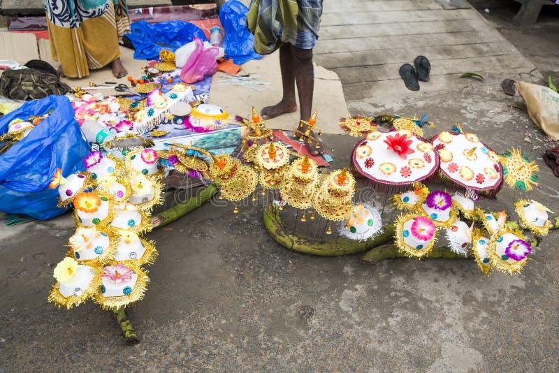 卖鲜花,菜,果子,献身者的伞的供营商能保佑印度神Ganesh在地方市场上在第一天 免版税库存照片