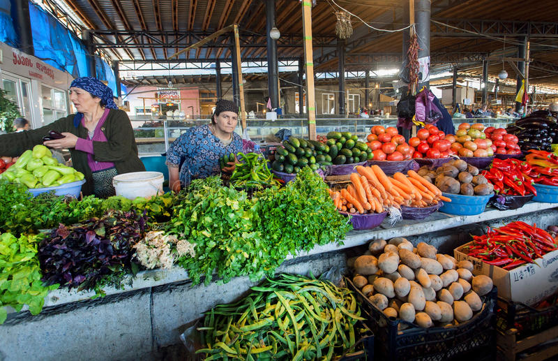 卖水果和蔬菜在市场里面的村庄妇女与新鲜的农夫` s产品 库存照片