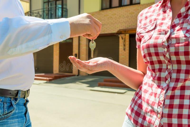 卖主送房子钥匙新所有者手 免版税库存照片
