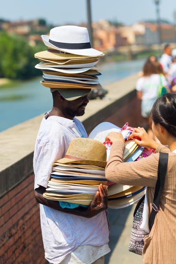 卖sunhats的深色皮肤的人在佛罗伦萨,意大利 免版税图库摄影