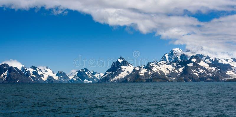 南乔治亚山和海岸线美好的全景从海,蓝色大西洋,雪coved山,蓝色sk 库存照片