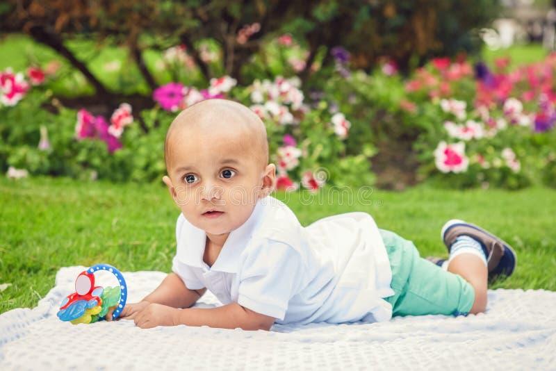 南亚印地安男婴在地面的公园 库存图片
