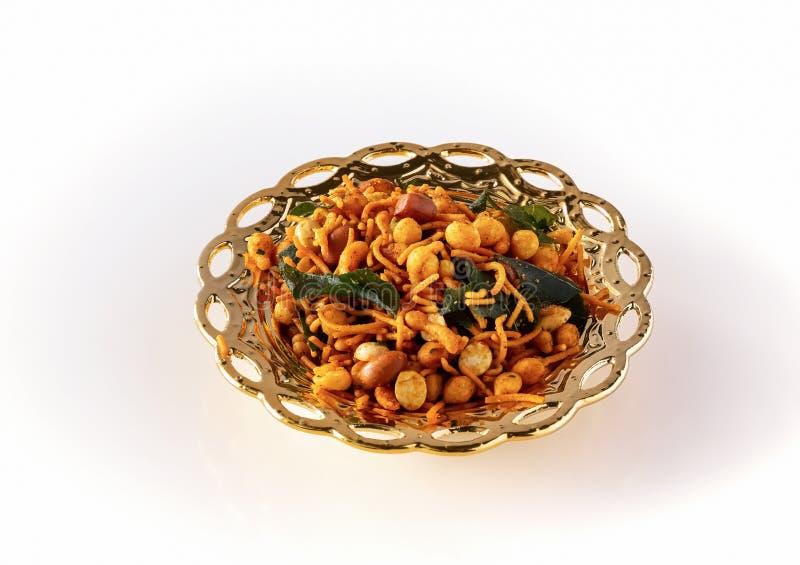 南印度辣嘎吱咬嚼的混合Nimco或Namkeen用花生,米,咖喱叶子和加香料被隔绝的金黄碗背景 免版税库存照片