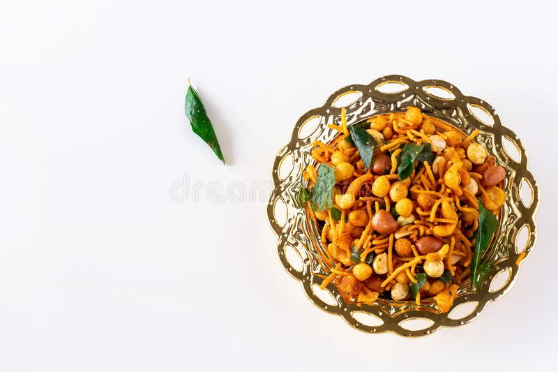 南印度辣嘎吱咬嚼的混合Nimco或Namkeen用花生,米,咖喱叶子和加香料金黄碗背景被隔绝的顶视图 库存图片
