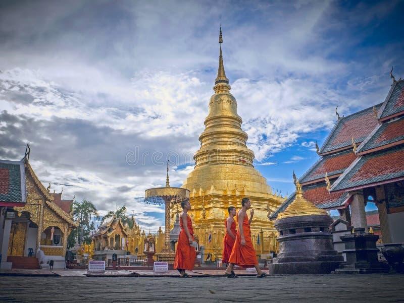 南奔,泰国- 2016年6月6日:走在有背景金黄塔的寺庙在Wat Phra的三名修士骇黎朋猜, 库存图片