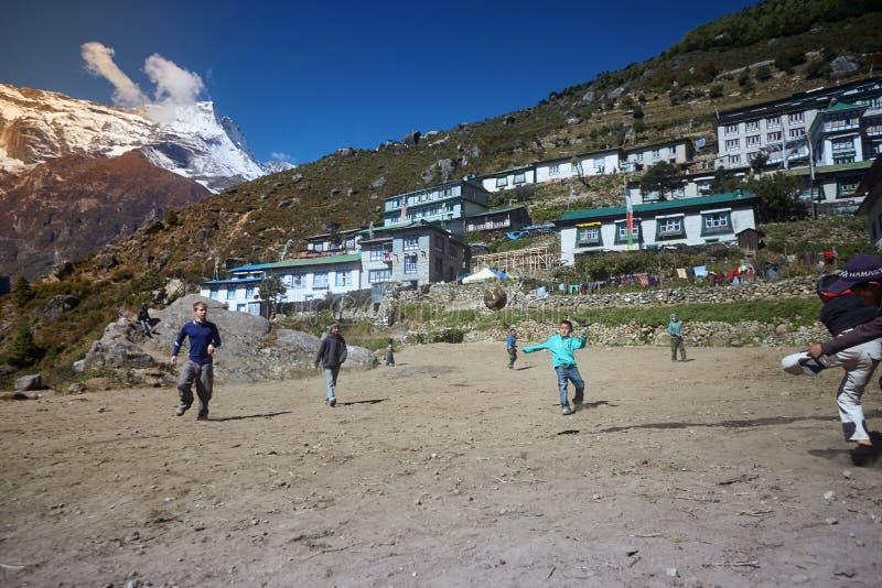 南崎巴札,尼泊尔- 2015年10月17日:踢在多灰尘的操场,南崎巴札的未知的孩子橄榄球 免版税图库摄影