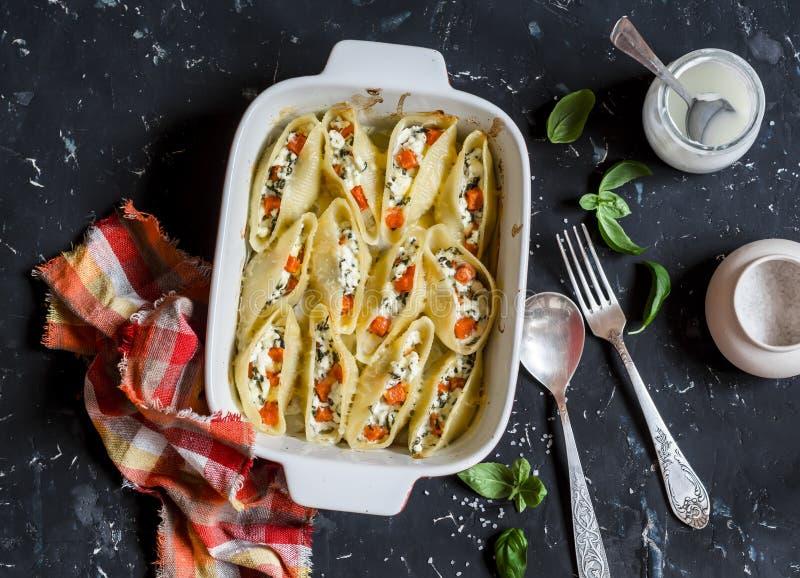 南瓜、乳清干酪和菠菜充塞了在烘烤盘的壳 项目符号 库存照片