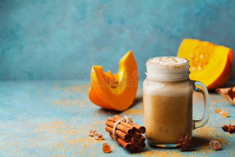 南瓜加了香料拿铁或咖啡在玻璃在绿松石葡萄酒桌上 秋天、秋天或者冬天热的饮料 舒适早餐或快餐 库存照片