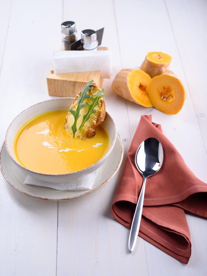 南瓜奶油色汤用在一块白色板材的巴马干酪多士 在白色桌上的南瓜片 在餐馆的午餐 免版税库存图片