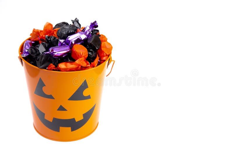 南瓜桶充满各种各样的被包裹的糖果 免版税库存图片
