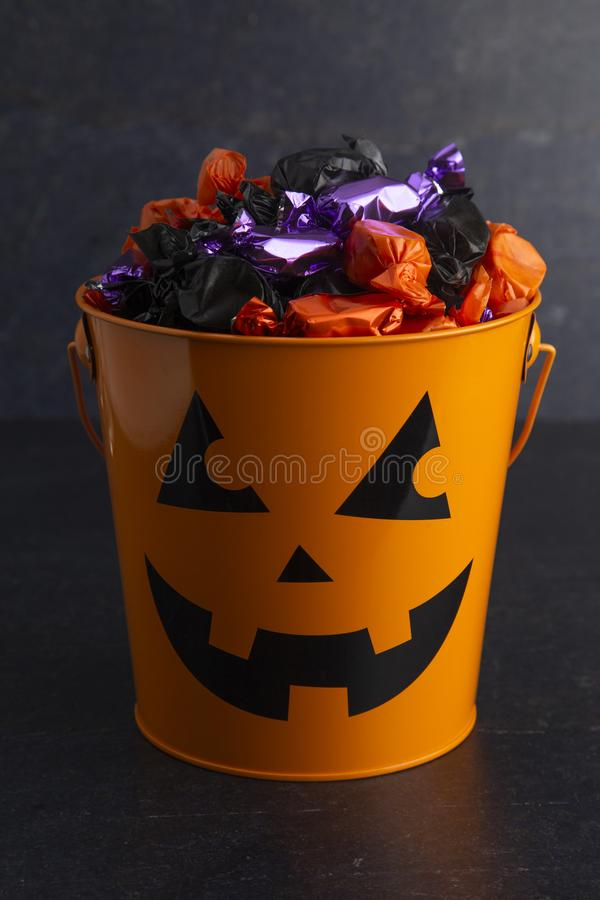 南瓜桶充满各种各样的被包裹的糖果 免版税图库摄影