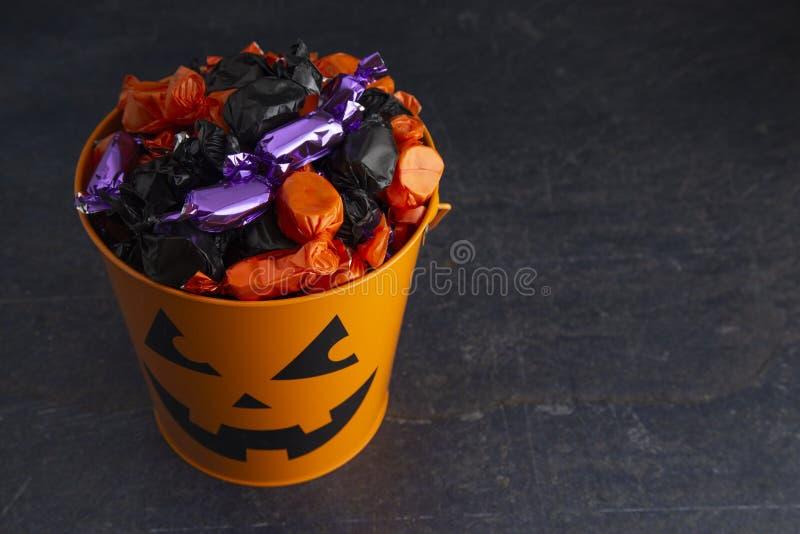 南瓜桶充满各种各样的被包裹的糖果 免版税库存照片