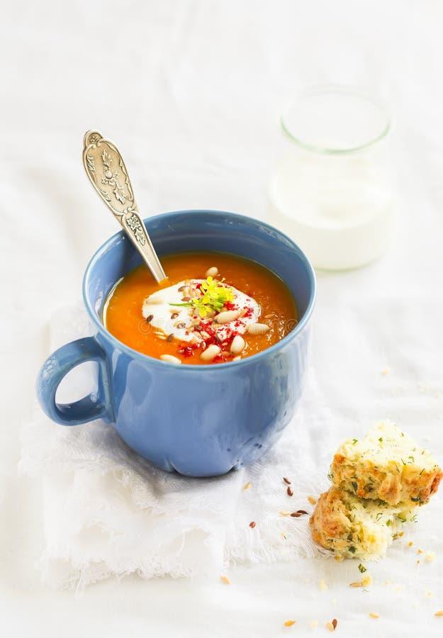 南瓜汤在有奶油和辣椒粉的蓝色陶瓷杯子服务 库存照片