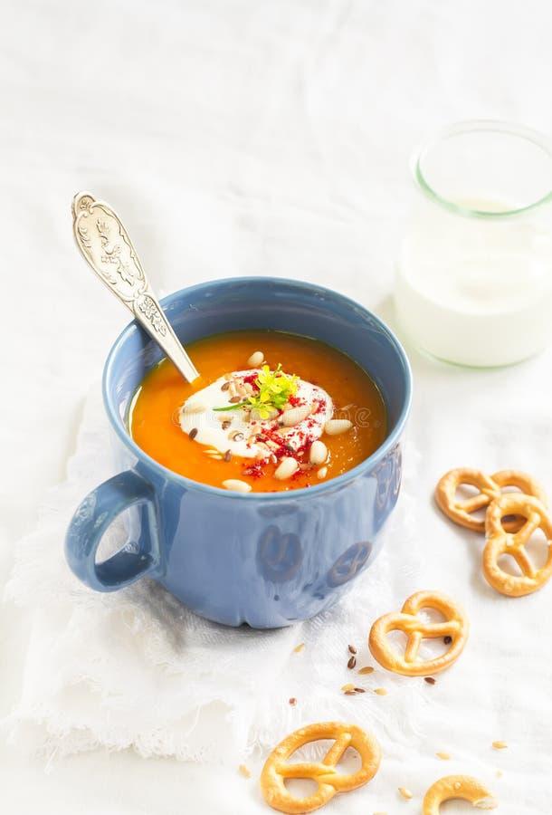 南瓜汤在有奶油和辣椒粉的蓝色陶瓷杯子服务 库存图片