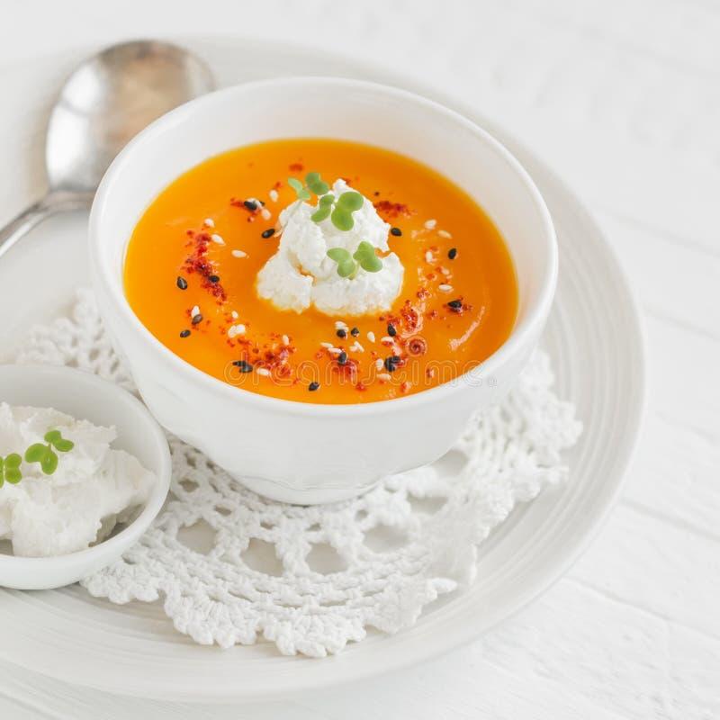 南瓜汤用辣椒粉和奶油在一个白色碗 图库摄影