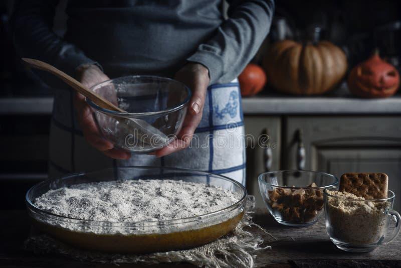 南瓜转储蛋糕的面团在木桌上的烘烤盘 免版税图库摄影