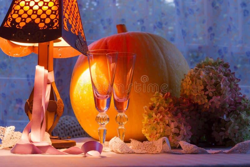 南瓜,玻璃杯子、八仙花属、fonr和灯温暖的光 Romant 免版税库存照片
