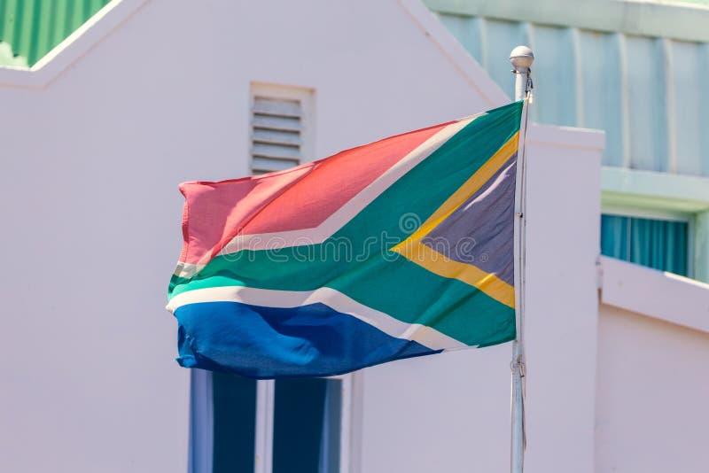 南非和传统白色修造的背景旗子  免版税图库摄影