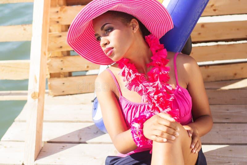 南非女孩在海附近戴桃红色帽子 免版税库存照片