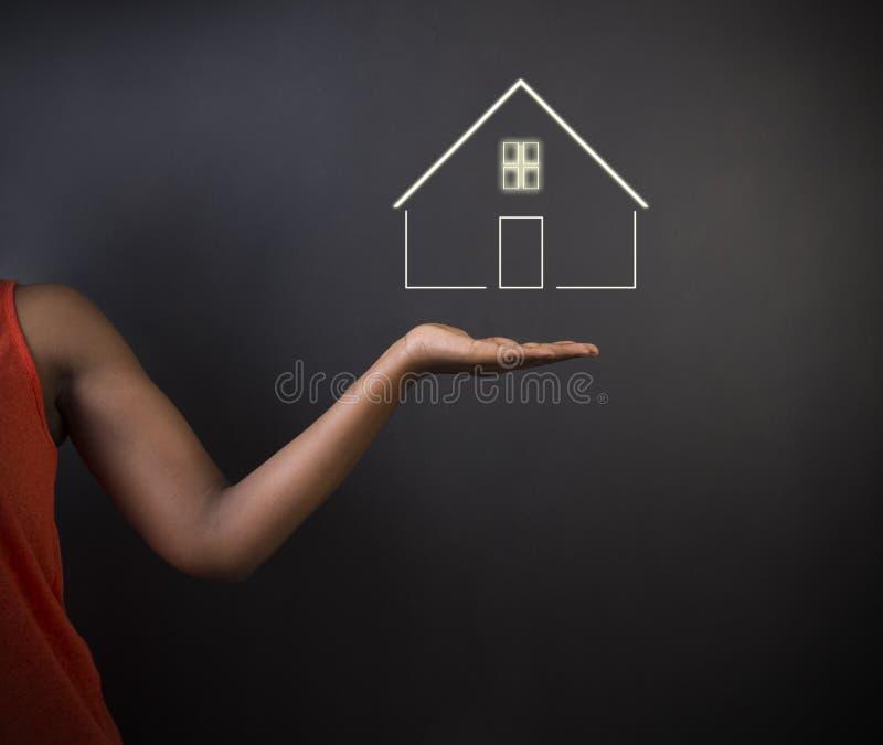 南非或非裔美国人的妇女老师或学生反对黑背景与家庭房子或房地产 免版税图库摄影