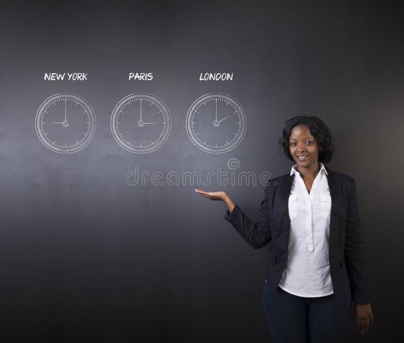 南非或非裔美国人的妇女老师或学生有纽约巴黎和伦敦的用粉笔写时区时钟在黑板 免版税库存照片
