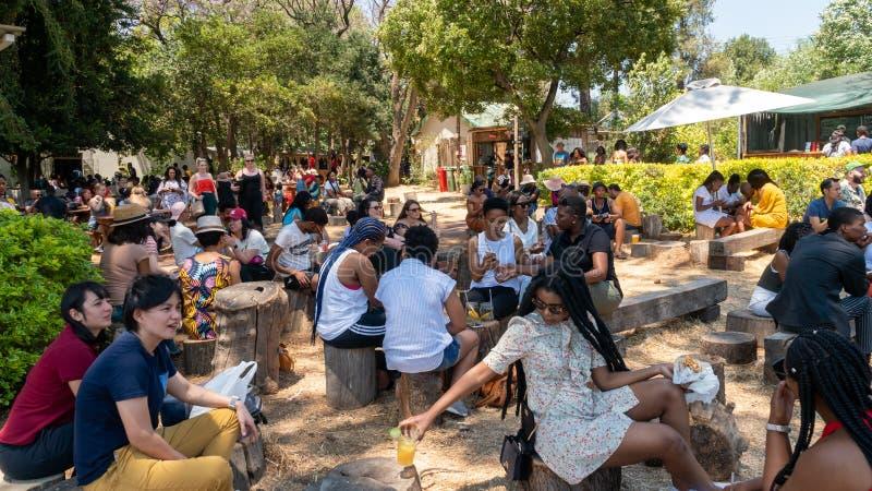 南非约翰内斯堡Fourways Farmers Market的人们吃饭和社交 库存图片