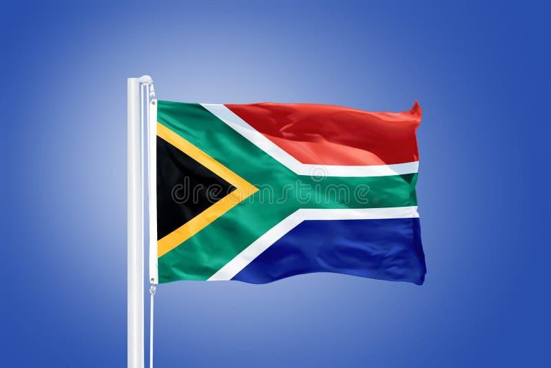 南非飞行旗子反对蓝天的 库存图片