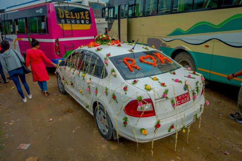 博克拉,尼泊尔双十国庆, 2017年:美丽的汽车用庆祝一个尼泊尔婚礼的花和村民装饰了  免版税库存图片