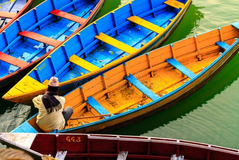 博克拉,尼泊尔- 2015年11月21日:人在五颜六色的小船坐Phewa湖在博克拉 免版税库存图片