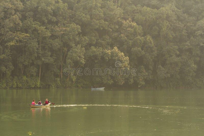 博克拉,尼泊尔- 2015年11月20日:游人在横跨Phewa湖的一条小船荡桨 免版税库存照片