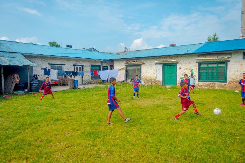 博克拉,尼泊尔- 2017年10月06日:踢足球在后院和穿制服,接近的未认出的孩子 免版税库存照片