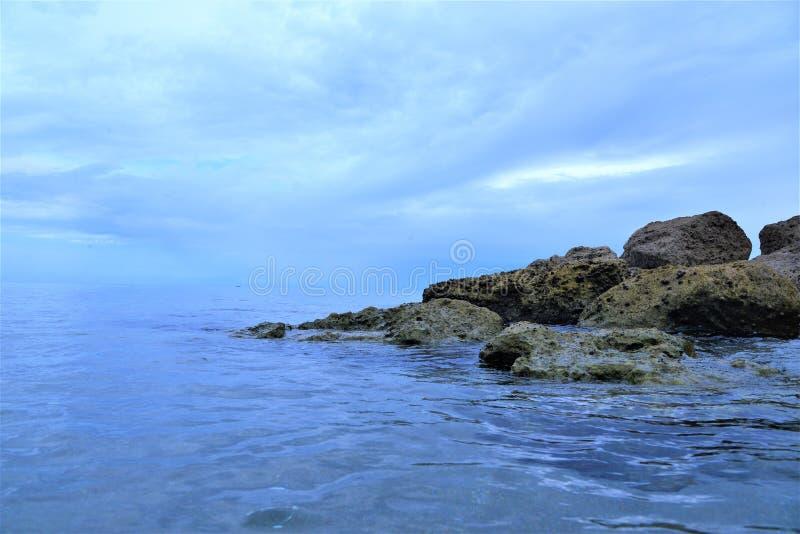 博察Raton,佛罗里达海滩有岩石由海浪轻轻地舔的一个特别区域 免版税库存照片