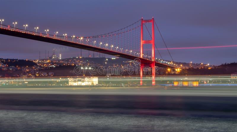 博斯普鲁斯海峡桥梁在与通过船轻的足迹的晚上,伊斯坦布尔土耳其 库存照片