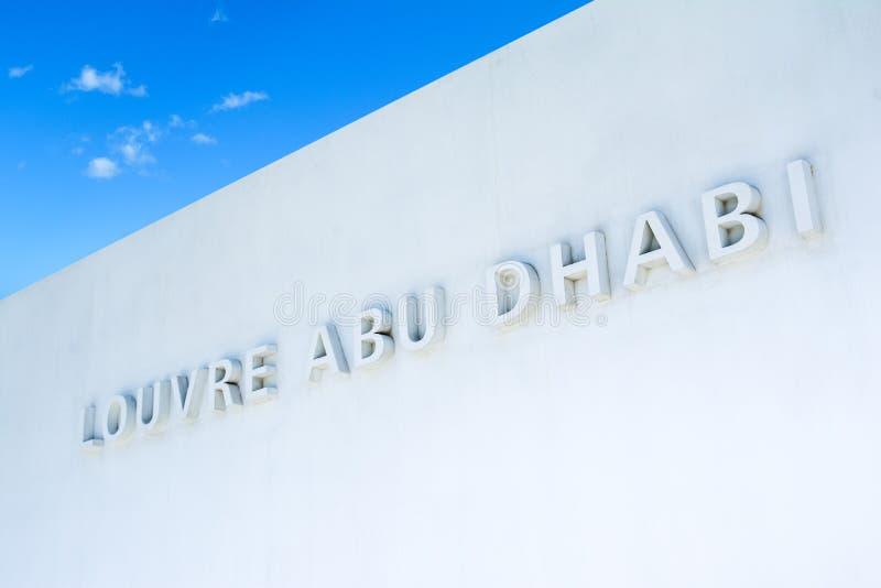 博物馆的名字在白色墙壁上的在天窗阿布扎比 库存图片