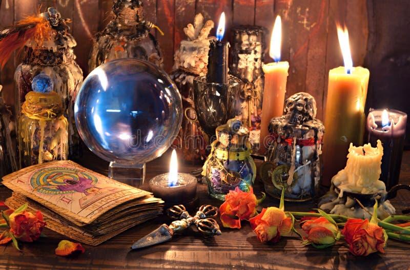 占卜用的纸牌、灼烧的蜡烛、巫婆不可思议的瓶和水晶球 免版税库存照片