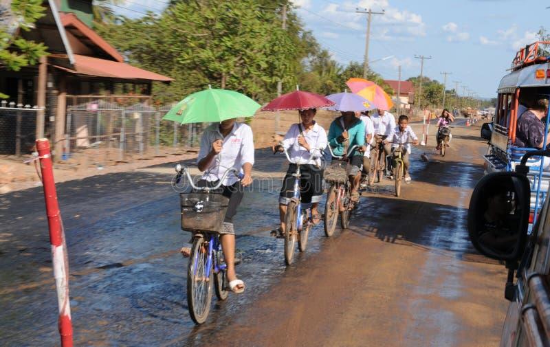 占巴塞省:骑自行车与一把伞的老挝人人在一只手上 库存图片