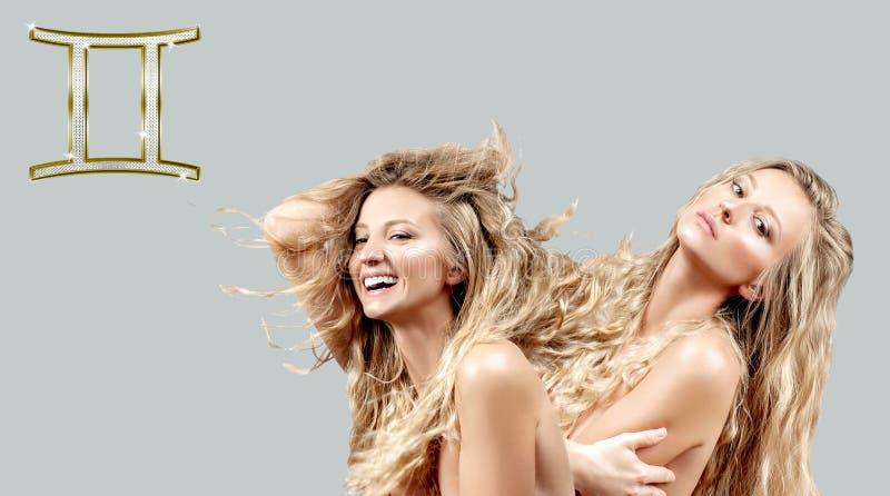 占星术和占星 双子星座黄道带标志,有卷曲长发的两美女 免版税库存照片