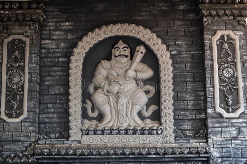 占碑省,印度尼西亚- 2018年10月7日:佛教神被雕刻的雕象在Vihara Satyakirti墙壁上的 免版税库存图片