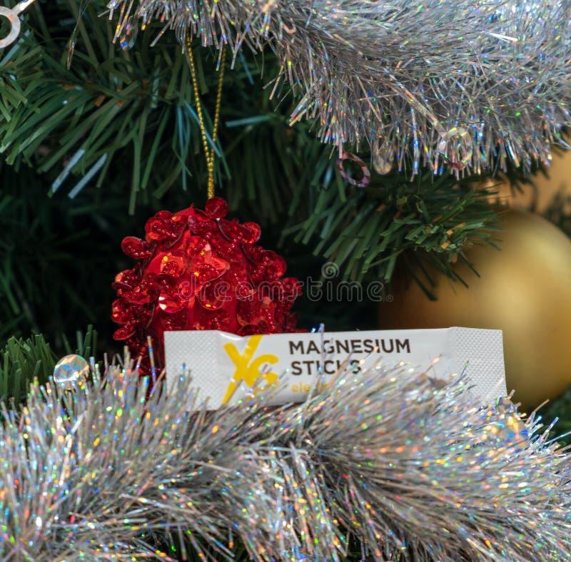 卡利亚里,意大利- 2018年12月:XS体育营养在圣诞树的镁棍子 自然的纽崔莱和素食主义者补充 免版税库存照片