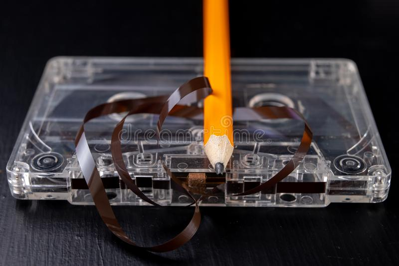 卡型盒式录音机和铅笔在一张黑桌上 老磁性数据载波 图库摄影