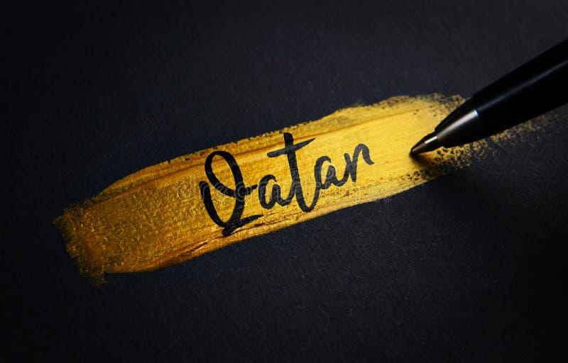 卡塔尔在金黄画笔冲程的手写文本 库存照片